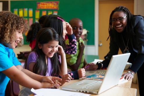 estudiantes sonriendo trabajando juntos en la computadora portátil