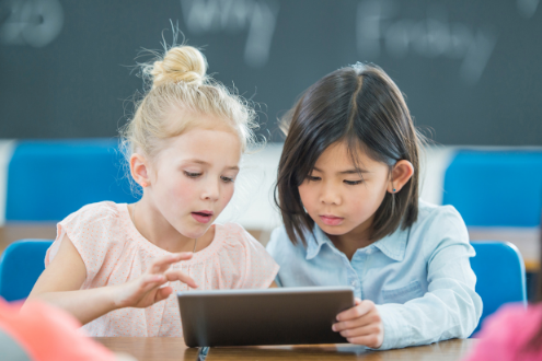 Two young girls play a game on a digital tablet