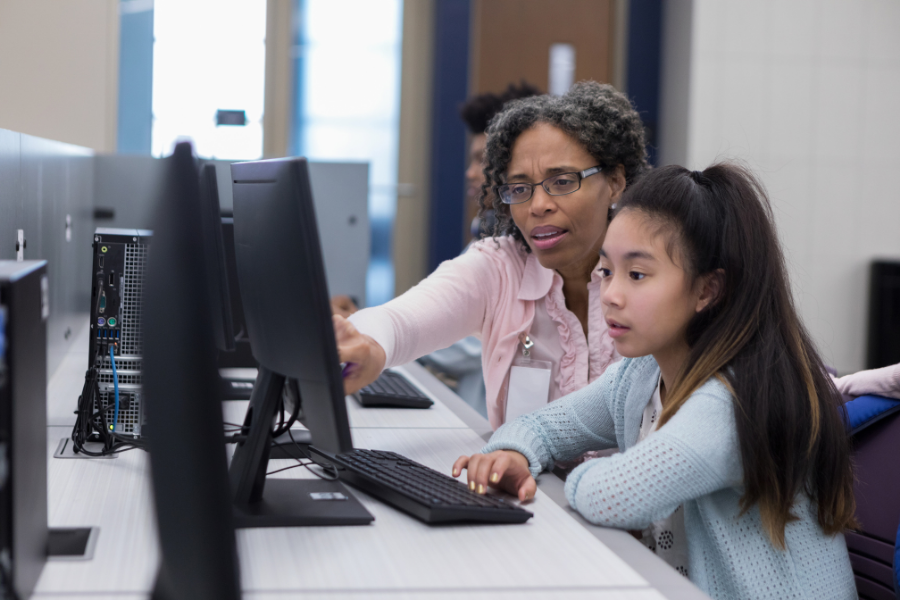 A teacher shows students something on a desktop computer