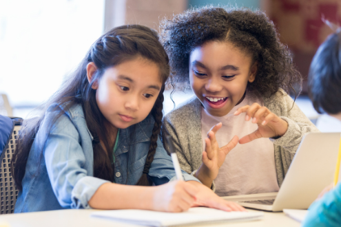 Two young students work together taking notes