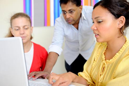 Three teachers surround a laptop