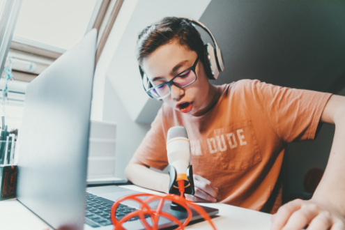 A teen boy podcasting