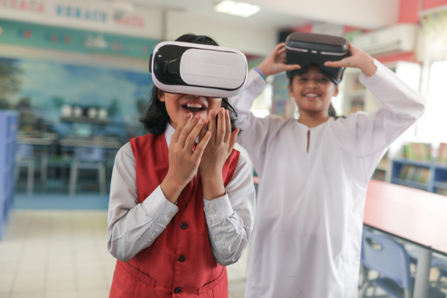 Two students in a classroom wearing VR head gear