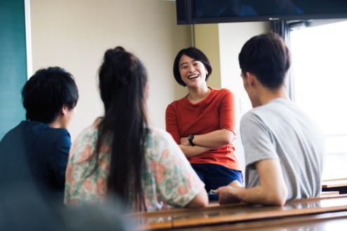 A student shares a laugh with three other students
