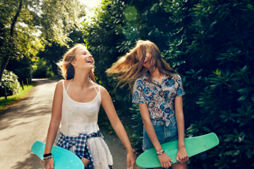 Two girls carrying skateboards laughing