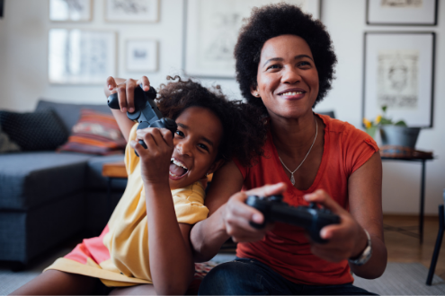 A girl plays a video game with her mom