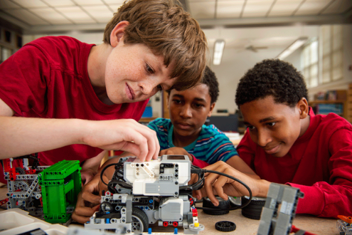 3 boys tinker with electronics in a school makerspace