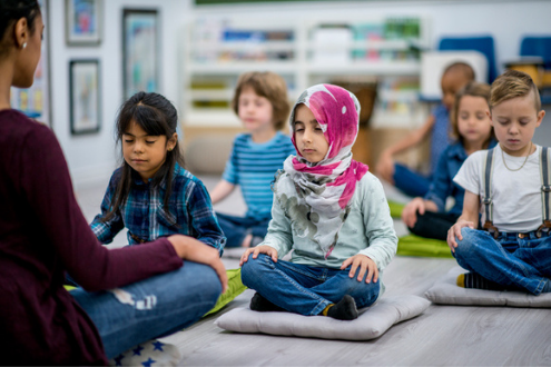 Students sit on mats to meditate in school