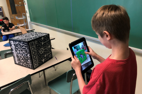 A boy uses a merge cube in the school library
