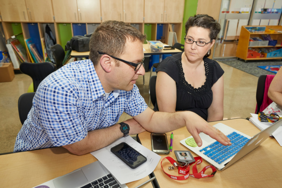 A school principal and a teacher work on a learning plan together.