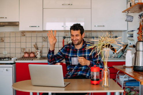 A man sits at a laptop in his kitchen waving o people attending a virtual conference.