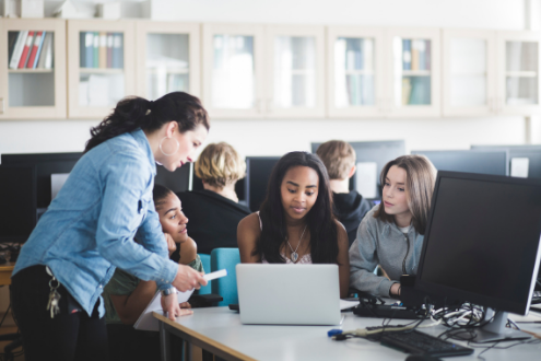 A teacher helps students on a laptop