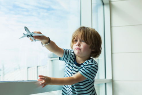 a boy plays with a toy plane at the airport