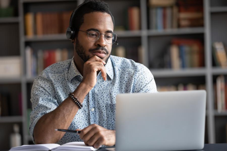 Un maestro ve las grabaciones de la conferencia en una computadora portátil