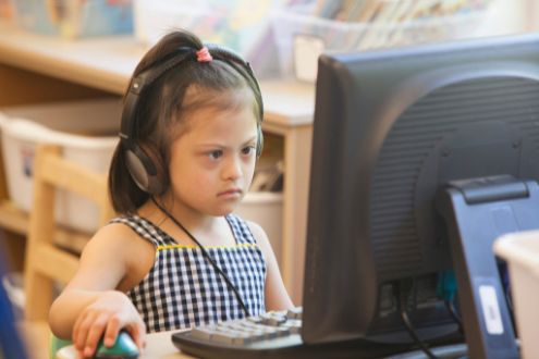 A girl is wearing headphones while using a desktop computer