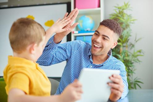 A teacher high fives a student
