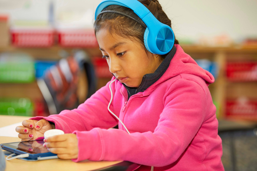 A girl listens to a book on her tablet