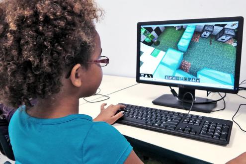 A girl plays Minecraft on a desktop