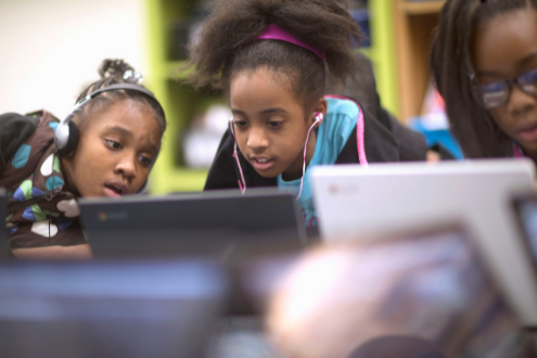 Three girls work together at a laptop