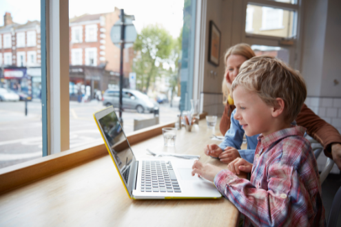 A boy uses a laptop in a cafe to do school work