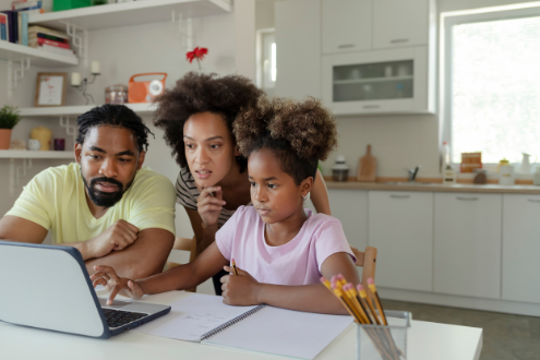 Two parents help a daughter with homework on a laptop in the kitchen