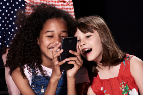 two students smile excitedly as they look at a phone