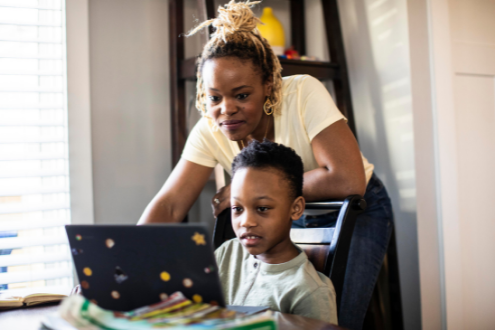 A mom and her son look at a website together on a laptop
