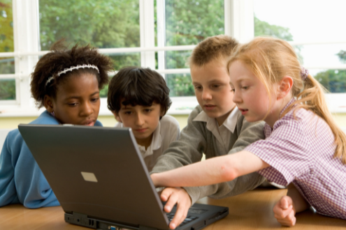 A group of four school children work together at a laptop