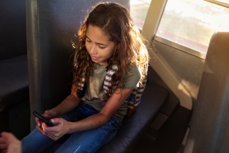 a girl reads on her phone on a bus