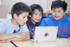 Three elementary school boys huddled around a laptop