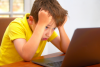 a frustrated boy looking at a laptop with his head in his hands
