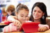 A teacher helps a student with the iPad